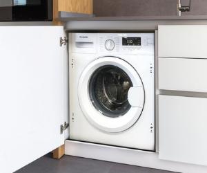 Integrated white washing machine behind cupboard door