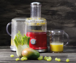 KitchenAid red juicer with selection of fruit and vegetables